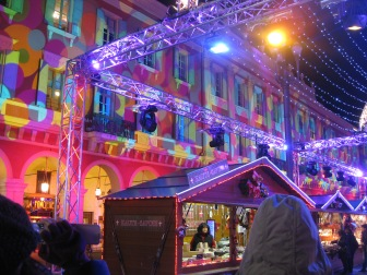 One of the booths at the Christmas market, and a light show on the building behind it!